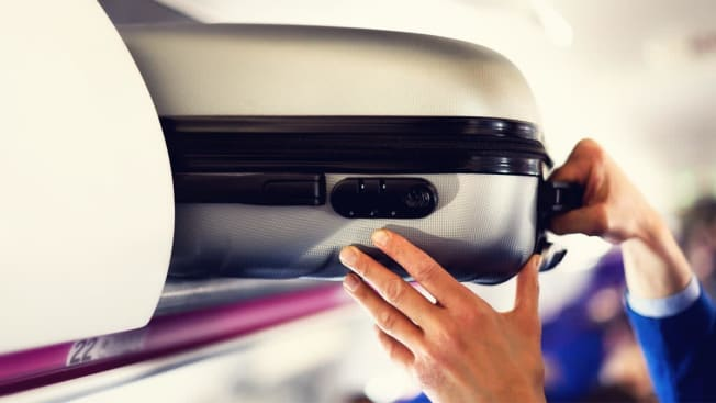 Carry on luggage being stowed in overhead compartment