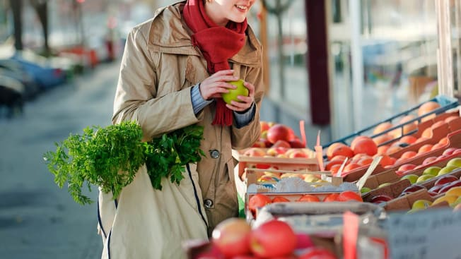 person shopping at farmer's market carrying tote bag and holding granny smith apple