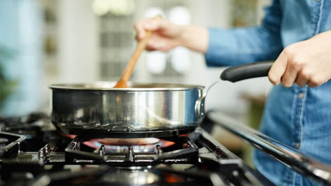 person cooking on a gas range, stirring with wooden spoon