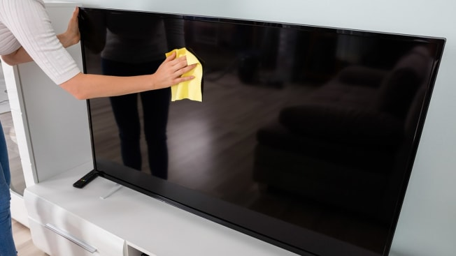 Person wiping TV screen with cloth