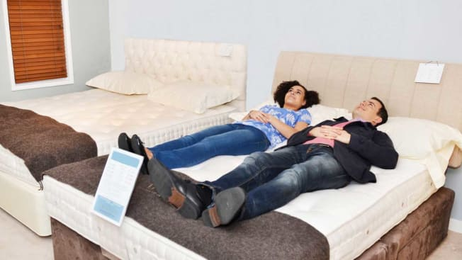 Couple laying on mattress in store