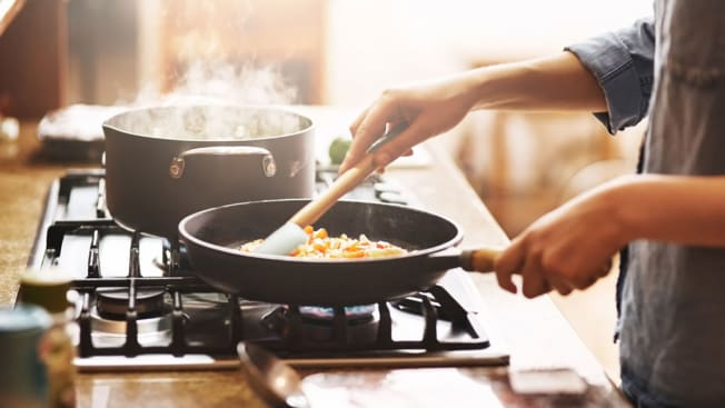 Person cooking on a stovetop.