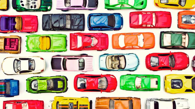 Toy cars of various colors and types lined up in grid pattern