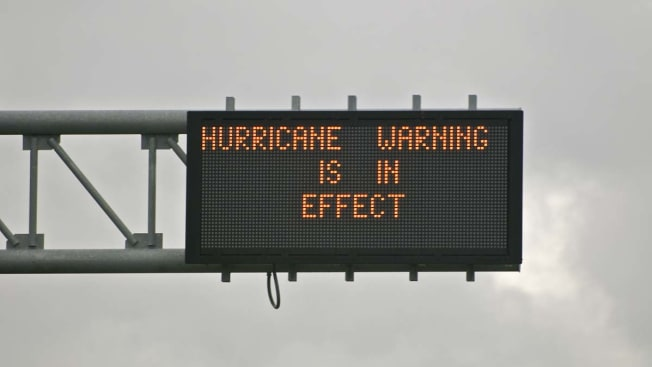 """A sign on the highway that says """"Hurricane Warning is in Effect"""""""