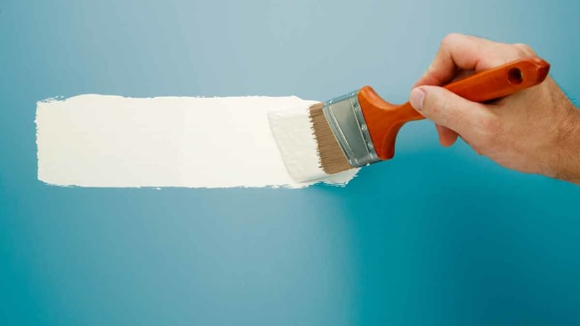 hand holding paint brush, painting wall