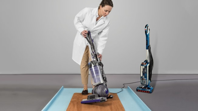 person holding upright vacuum on carpet sample designed for testing