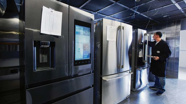Test technician examining the inside of a refrigerator with other refrigerators in foreground