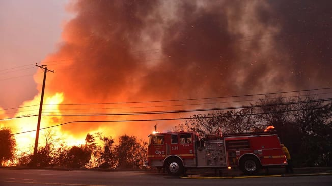 A firefighter stands near his truck as smoke rises above Pacific Coast Highway (Highway 1) during the Woolsey Fire on November 9, 2018 in Malibu, California. -