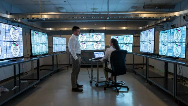 test technicians in TV lab surrounded by multiple TVs on tables