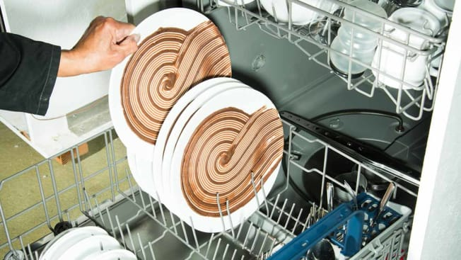 Tester placing dirty dish in dishwasher.