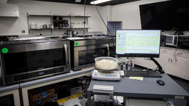 Computer screen with testing data in lab with bowl of popcorn on scale and over the range microwaves in the background.