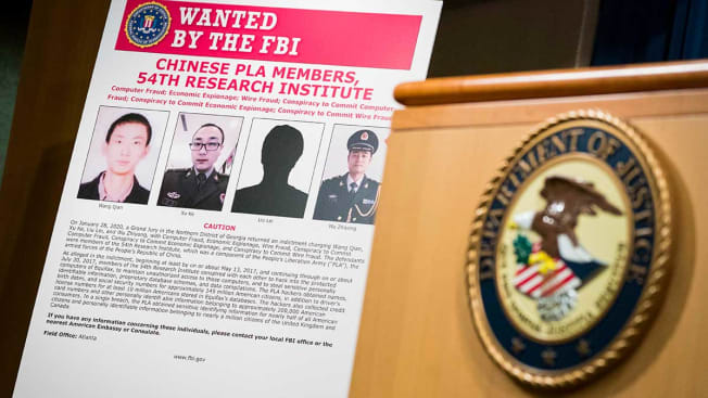Signs that depict the four members of China's military indicted on charges of hacking into Equifax Inc. and stealing data from millions of Americans are seen shortly after Attorney General William Barr held a press conference at the Department of Justice on February 10, 2020 in Washington, DC. (Photo by Sarah Silbiger/Getty Images)
