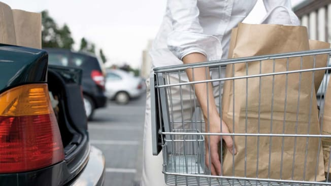 woman loading groceries in car