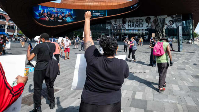 A protester holding a sign and a fist raised in the air outside the Barclays Center. Protesters took to the streets across America after the killing of George Floyd at the hands of a white police officer that was kneeling on his neck during his arrest as he pleaded that he couldn't breathe. The protest are attempting to give a voice to the need for human rights for African American's and to stop police brutality against people of color. Photographed outside the Barclays Center in the Brooklyn Borough of New York on May 30, 2020, USA.