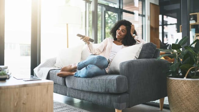 person sitting on couch holding remote, watching tv
