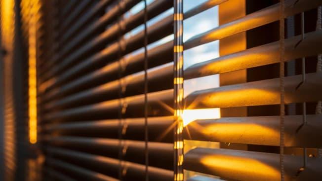 Sunlight coming through open window blinds.