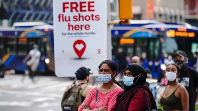 An advertisement offering free flu shots is seen during the protest. Families grieving the loss of their loved ones by the pandemic organized a 'March for the Dead' in New York City to mourn over 175,000 Americans who lost their lives during the coronavirus pandemic under the Trump administration. (Photo by John Nacion/SOPA Images/LightRocket via Getty Images)