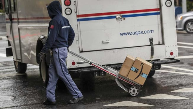 A U.S. Postal Service (USPS) worker delivers Amazon boxes in New York, U.S., on Tuesday, Oct. 13, 2020. Amazon.com Inc.'s two-day Prime Day sale kicks off on Tuesday and is expected to give the world's largest e-commerce company an early advantage over brick-and-mortar rivals still contending with pandemic-spooked consumers wary of battling Black Friday crowds.