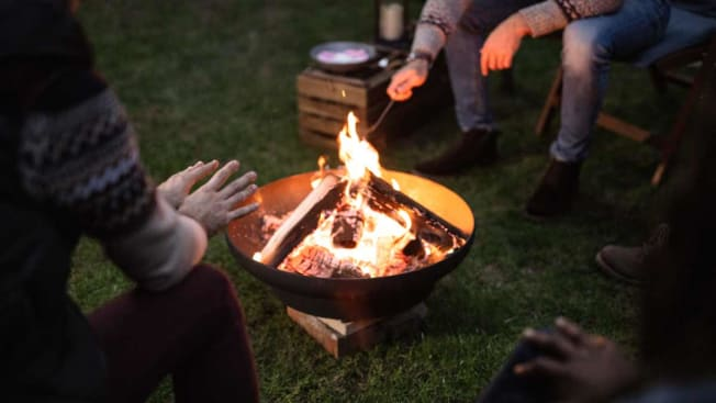 people socially distant around fire pit
