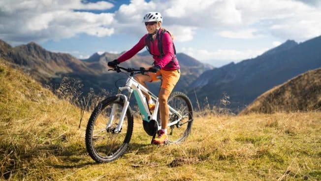 Woman with helmet on ebike mountain biking