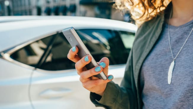 woman at car dealer checking pricing on her smartphone