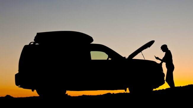 Car with hood open at sunset and person standing in front looking at phone