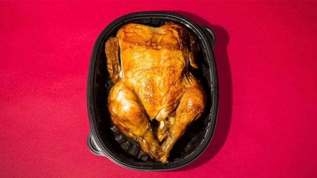Rotisserie chicken in container on dark pink background