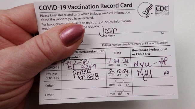 Patient holding Covid 19 vaccinated record card.