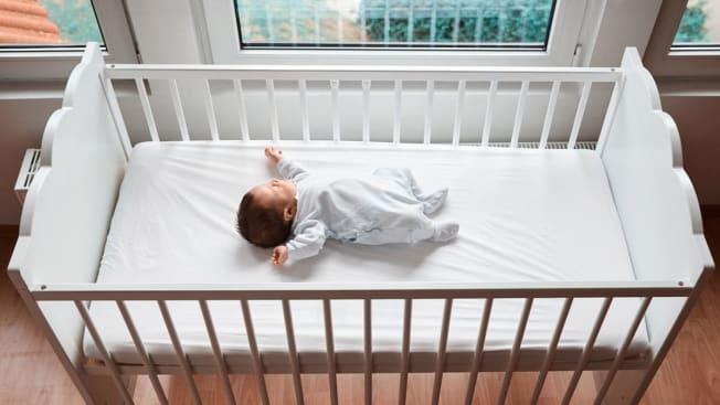 baby in bare crib