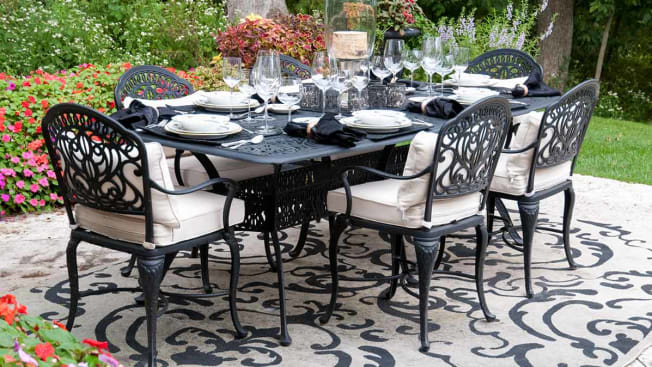 An outdoor table set for a meal sits on top of an outdoor rug