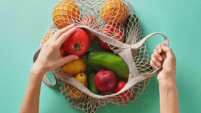 hands holding meshed fabric bag with various fruits and vegetables