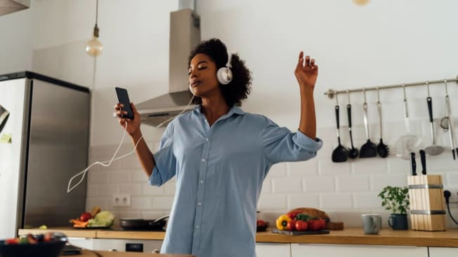 A person in a kitchen wearing a pair of wired headphones while holding a smartphone