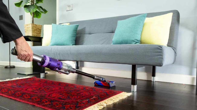 The Dyson Omni-glide stick vacuum cleaning under a grey couch on a wooden floor
