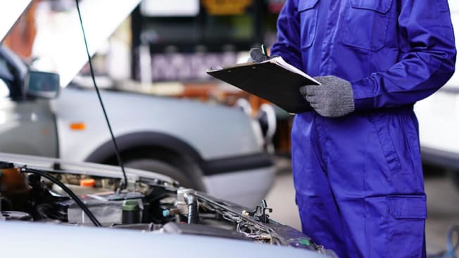 Mechanic inspecting a used car