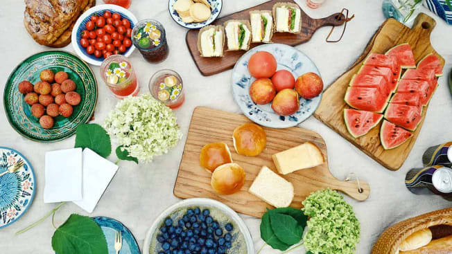 A picnic laid out with food on multiple ceramic plates and wooden cutting boards.