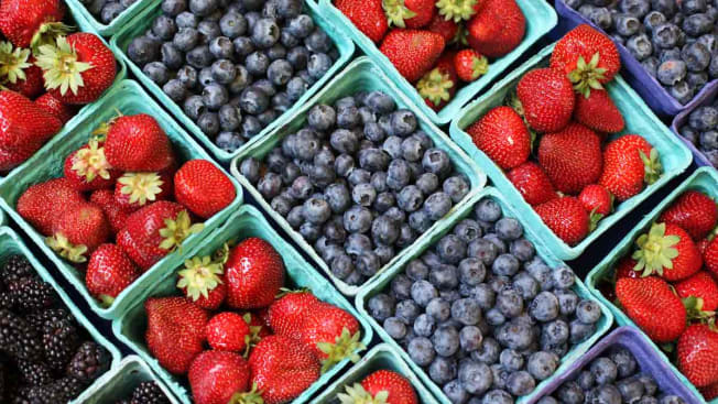 Cartons of fresh blackberries, strawberries, and blueberries on display at a market
