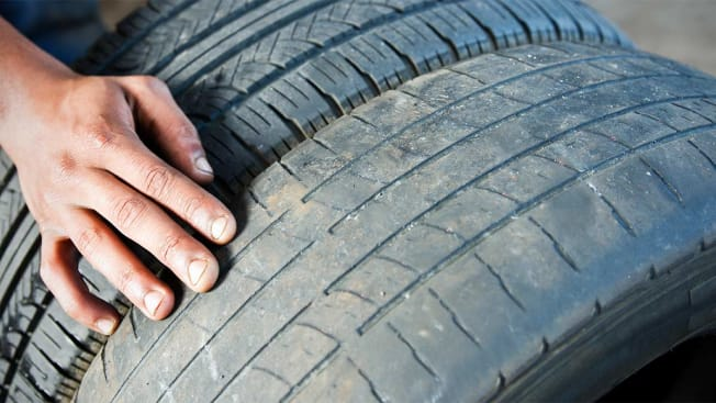 A person inspecting the tread on a worn tire.