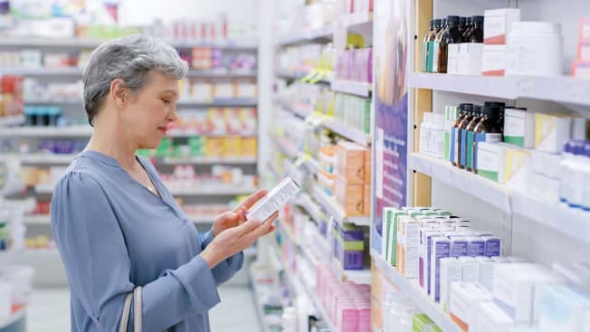 A person looking at over the counter medications in pharmacy aisle