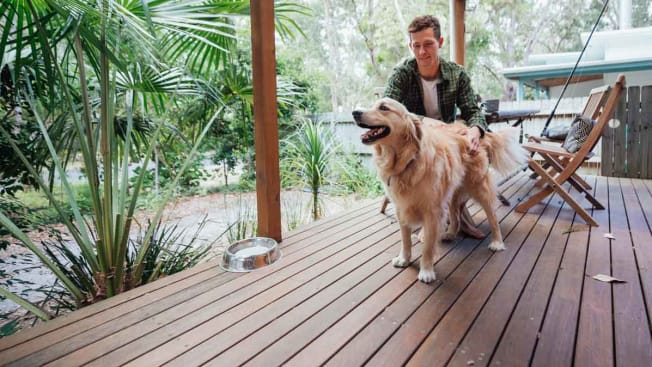 A person sitting at a table on a wood deck  while petting a dog