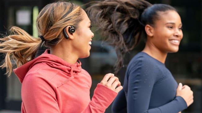 two people jogging side by side, one is wearing wireless earbuds