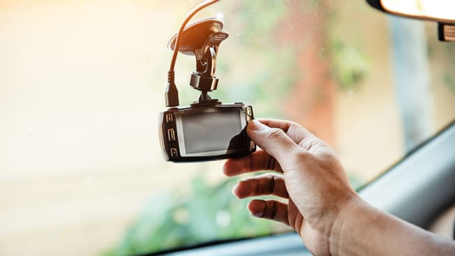 Person adjusting dash cam on their car's windshield.