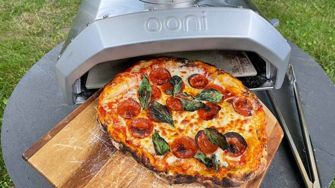 A finished pizza being slid out of the Ooni Pizza Oven on a wooden pizza peel