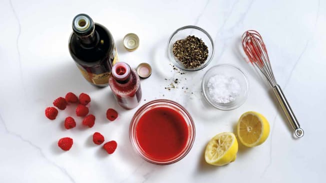 overhead of raspberry vinaigrette ingredients (raspberries, lemon, oil, salt, pepper) on marble countertop