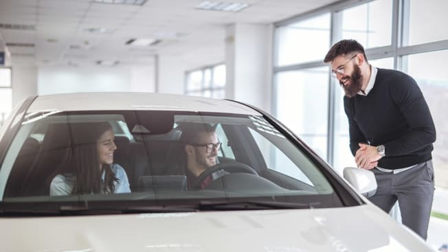 couple buying a new car at a car dealership and  talking to a car salesman