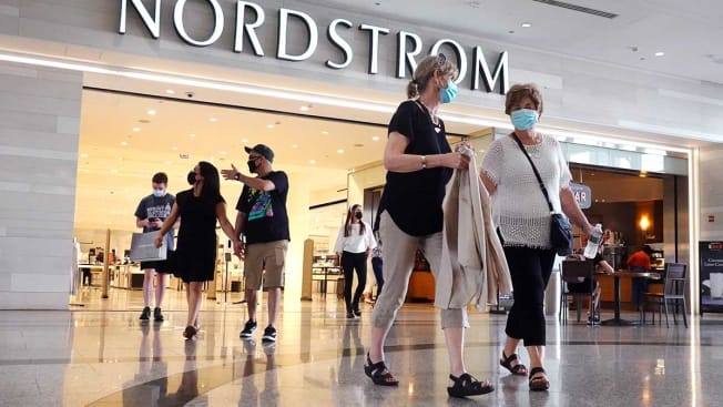 A number of shoppers wearing face masks leaving a Nordstrom inside a Chicago shopping mall.