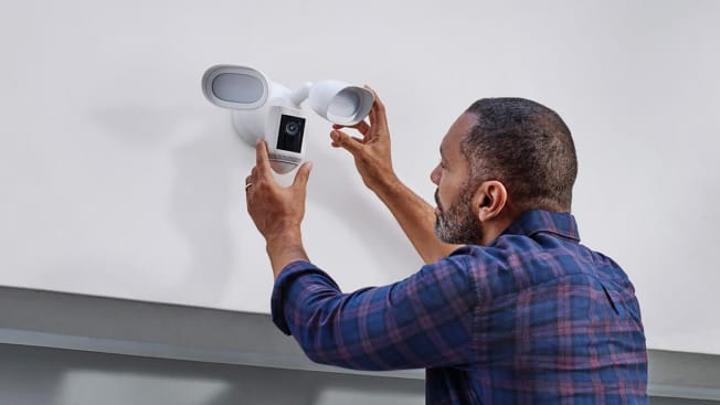 Person installing a Ring Floodlight security camera.