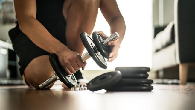 Person adding weight to an adjustable dumbbell.