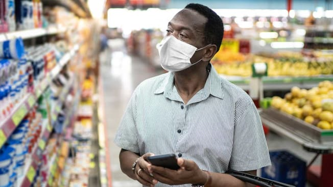Person shopping in a grocery store wearing a face mask.
