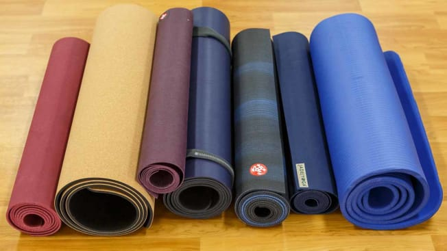 group of different types of yoga mats on gym floor