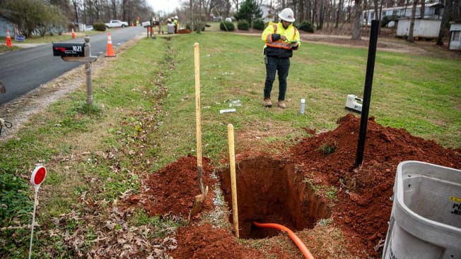 A technician checking the installment of fiber-optic cable that can be seen going through a large hole underground.